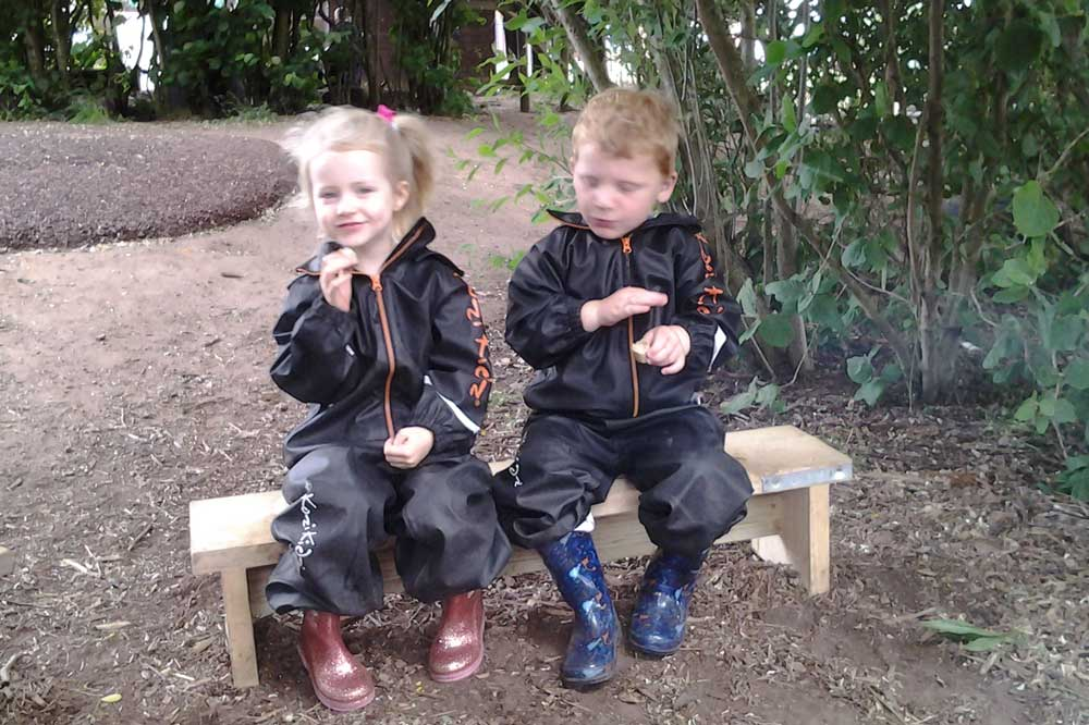 tots at forest school - two children sitting on a bench in full waterproofs